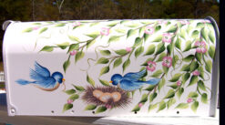 hand painted mailbox with blue birds pink flowers and nest
