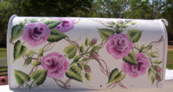 hand painted mailbox with pink roses on a trellis